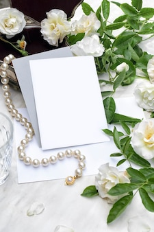 Mockup poster invitation flyer or greeting card with white roses on marble background and pearl necklace with silver jewelry box wedding stationery top view