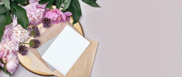 Макет плаката, пригласительный билет или поздравительная открытка с цветами пионов на золотом подносе, свадебные канцелярские товары на пастельном фоне, плоская планировка с копией пространства