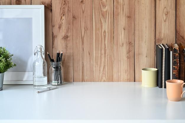 찻잔 및 사무실 액세서리와 함께 흰색 나무 책상에 모형 포스터