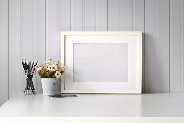 Mockup poster picture blank frame on white desk