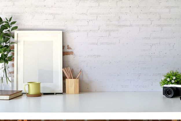 Mockup poster template with vintage camera, supplies on white desk workspace