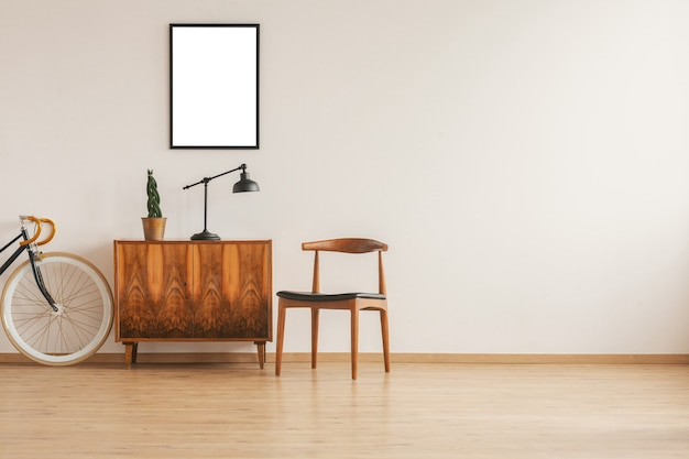 Mockup poster above vintage cabinet with lamp and plant in pot stylish wooden chair next to it
