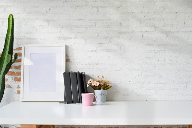 Mockup poster on white wooden desk with a mug and office accessories