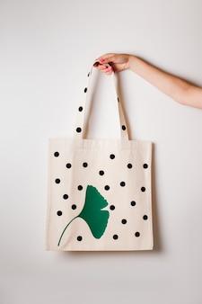 Мокап многоразовых продуктовых пакетов с принтом в виде большого черного горошка и зеленого листочка на белом изол ...