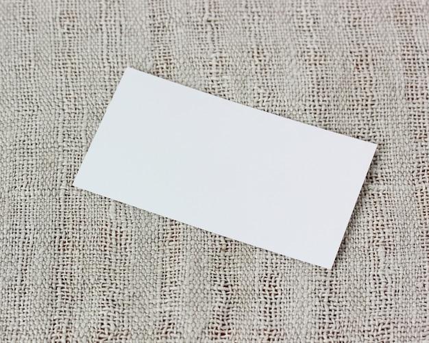 Мокап, создатель сцены. пустая визитная карточка на серой ткани, вид сверху.