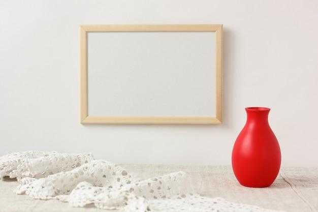 モックアップ、シーンクリエーター。壁の空のフレーム、レース、赤い花瓶。