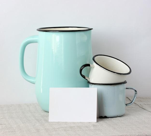 Мокап, создатель сцены. эмалированная посуда и белая пустая карточка на столе. кувшин и кружки. копировать пространство.