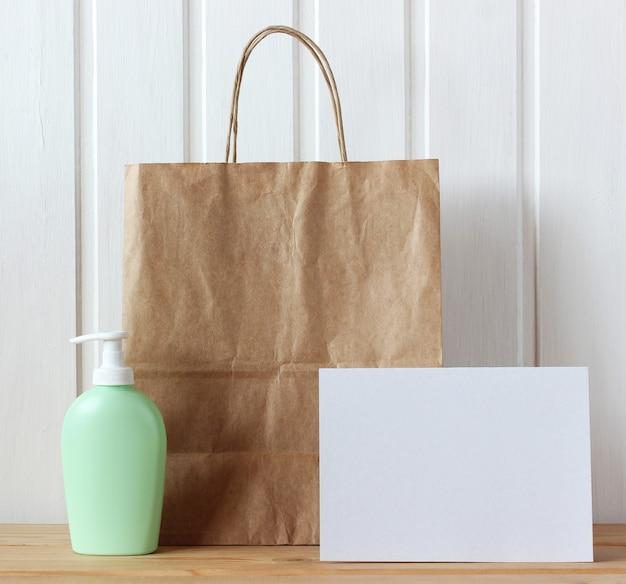 モックアップ、シーンクリエーター。紙袋、ディスペンサー付きプラスチックボトル、ライトのテーブルに空のカード。