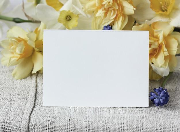 モックアップ、シーンクリエーター。白い空白のカードと黄色い水仙の束。