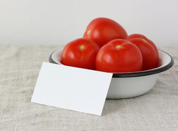 Мокап, создатель сцены. белая пустая карточка в миске с красными помидорами, выборочный фокус. копировать пространство.