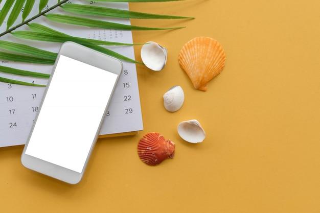 黄色の背景に海のシェルと熱帯の葉のモックアップ画面のスマートフォン