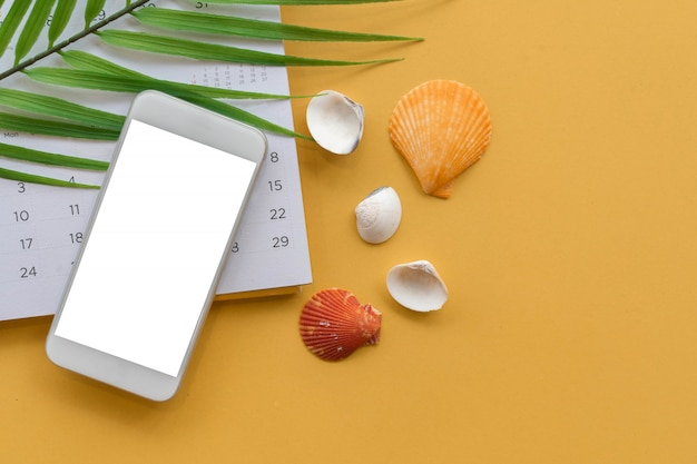 Mockup screen smartphone with sea shell and tropical leaves on yellow background