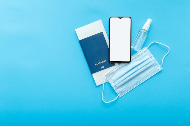 흉내낸 스마트폰 빈 화면 여권 비행기 티켓 의료 마스크와 소독제. 그린 패스 코비드 테스트 앱에 대한 모형. 개념 여행 예방 접종은 복사 공간이 있는 파란색으로 평평하게 놓여 있습니다. 고품질 사진