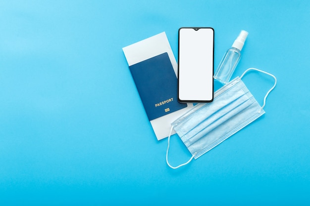 Mockup smartphone blank screen passport plane tickets medical mask and sanitizer. mockup for green pass covid test app. concept travel vaccination flat lay on blue with copy space. high quality photo