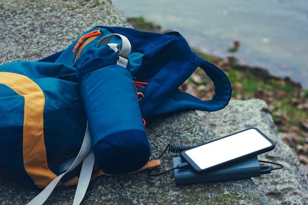 흰색 화면이 휴대용 충전기로 충전 된 모형 스마트 폰입니다.