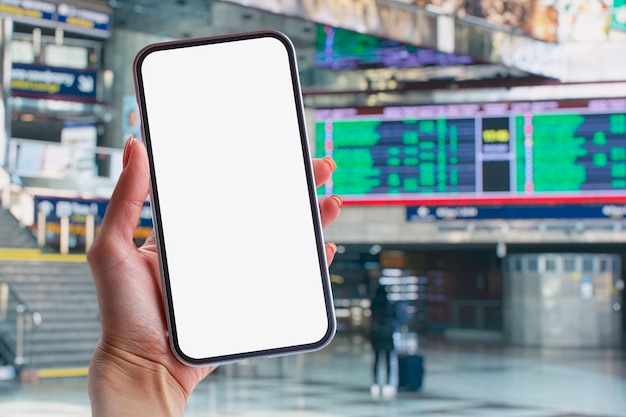 Mockup of a smartphone with a white screen close-up against the background of the timetable at the railway station.