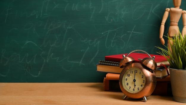빈티지 알람 시계, 나무 그림, 책, 녹색 칠판 배경 위에 식물이 있는 나무 탁자 위의 모형 공간. 다시 학교로, 공부 테이블