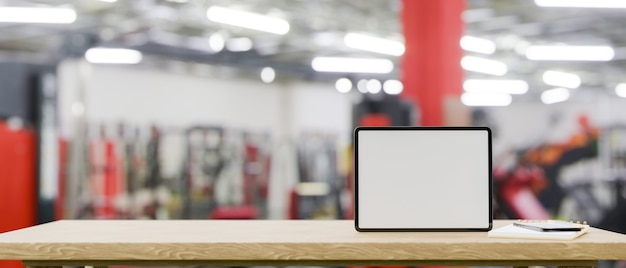 Mockup space on wooden tabletop with blank screen tablet mockup over blurred fitness gym