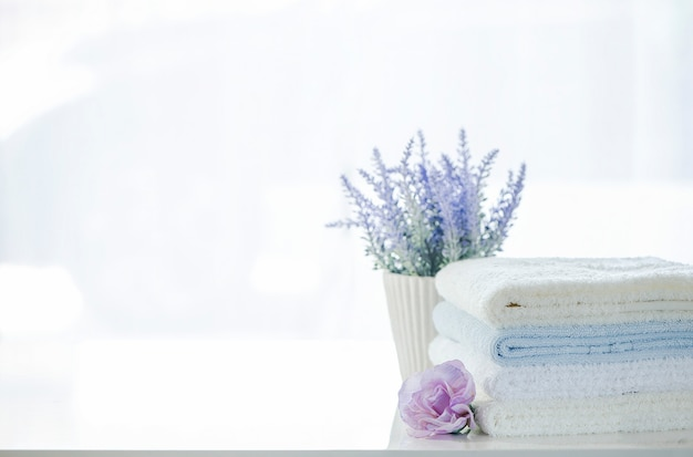 Mockup stack of white towels and flower on white table with copy space.