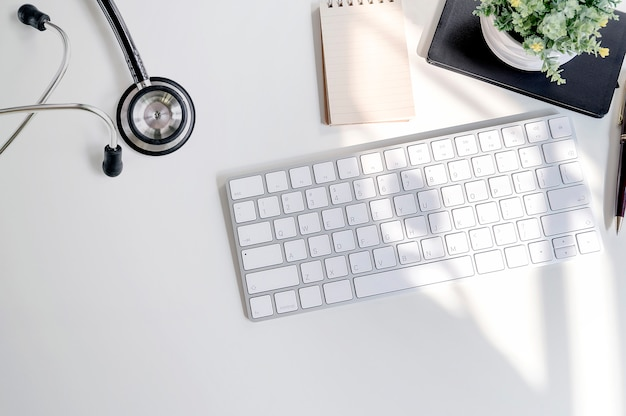 Mockup stethoscope with white keyboard and supplies on white table