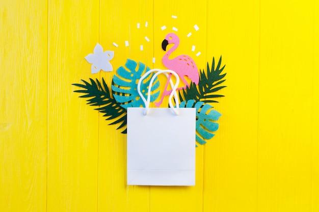 モックアップ夏熱帯は、黄色の木製の背景にフラミンゴ鳥と葉します。ジャングルのヤシとモンステラの葉