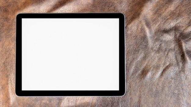 Пустой экран планшета макета на коричневой кожаной поверхности.