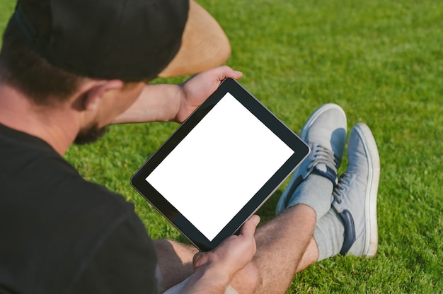 Mockup tablet in the hands of the guy. against the backdrop of a green lawn.