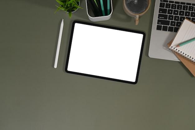 목업 태블릿은 최고의 사무실 책상과 함께 다양한 장비로 둘러싸인 업무용 책상에 놓여 있습니다.
