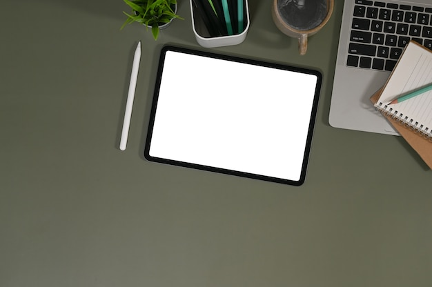 Mockup tablet is putting on a working desk surrounded by various equipment with top office desk.