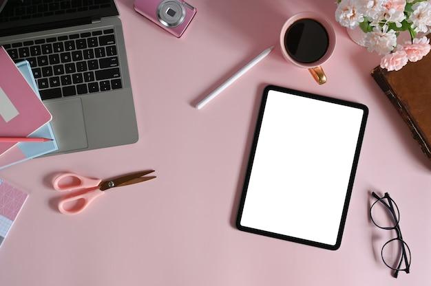 Таблетка-макет с пустым экраном и портативным компьютером различным женским оборудованием на женском рабочем пространстве.