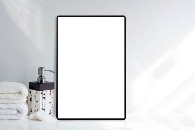 Mockup tablet with blank white screen and bath towel with soap on white table in white room,