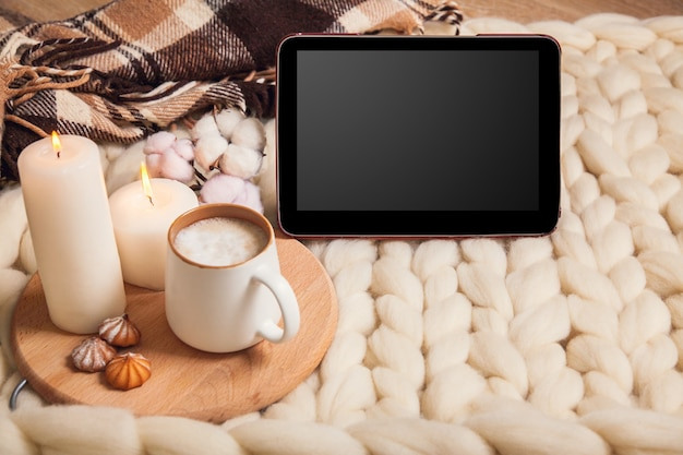Mockup tablet with cup of cappuccino and cookies, candles, checkered plaid on the background of blanket of thick yarn. the atmosphere of homeliness and comfort.