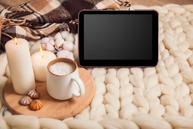 Макет планшета с чашкой капучино и печеньем, свечами, клетчатым пледом на фоне одеяла из толстой пряжи. атмосфера домашнего уюта и комфорта.