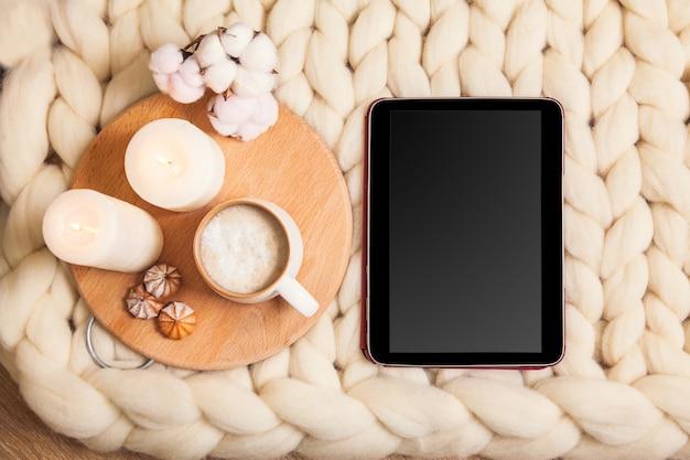 Таблетка-макет с чашкой капучино и печеньем, свечами, клетчатым пледом на фоне плоской планировки из толстой пряжи. атмосфера домашнего уюта и комфорта.
