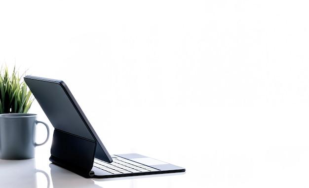 白い背景、タブレットの側面図に魔法のキーボード、マグカップ、観葉植物とモックアップタブレット。