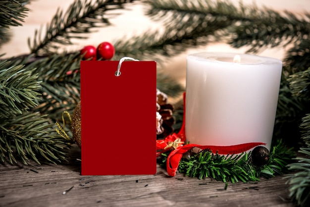 Mockup tag paper card with candle christmas decoration on wood table background.