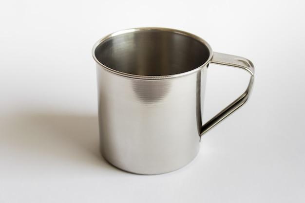 흰색 표면에 하나의 금속 컵 머그잔의 모형 템플릿 전면보기.