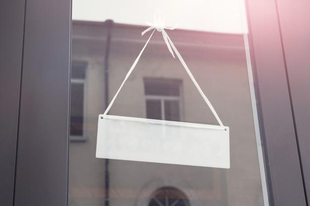 ショップのガラスのドアにメッセージボードをぶら下げのモックアップテンプレート