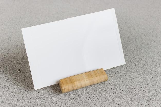 Шаблон макета с пустой фотокарточкой на деревянной подставке на серой точечной поверхности.