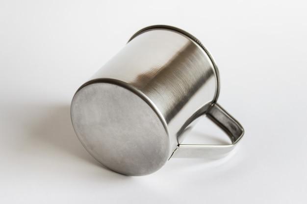 흰색 표면에 누워 금속 스테인레스 스틸 컵 모형 템플릿.