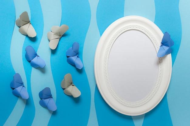 Шаблон макета с овальной белой рамкой со сложенными из бумаги бабочками оригами на синих бумажных слоях.