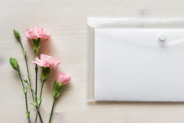 Mockup template with pink flowers and blank paper in plastic folder on wooden