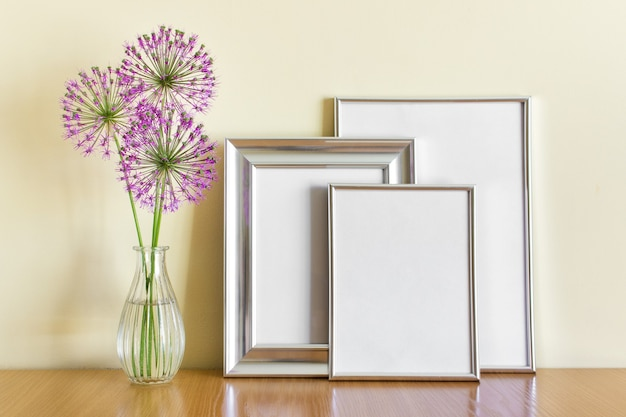 유리 꽃병에 은색 프레임과 분홍색 원형 여름 마늘 꽃이 서 있는 모형 템플릿입니다.