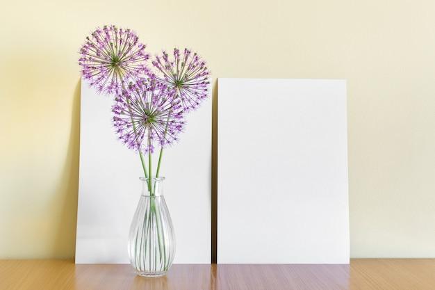Шаблон макета с двумя листами бумаги формата а4, стоящими рядом с желтой стеной с круглыми розовыми цветами чеснока в стеклянной вазе.