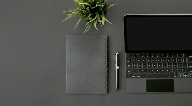 Mockup top view of tablet with keyboard, notebook, pen and houseplant on black background.