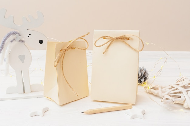 Mockup of two christmas kraft gift packages with tag on wooden background