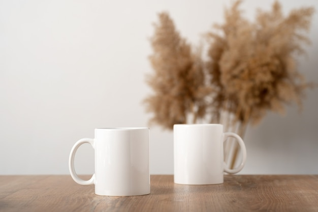 スカンジナビアのインテリア、自由奔放に生きるスタイルのパンパの装飾が施された木製のテーブルトップに2つの白いマグカップをモックアップします。