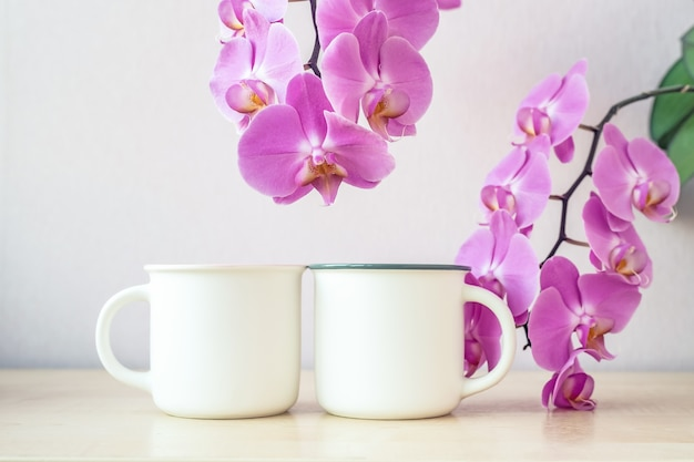 Mockup of two white mugs on table with orchid flowers decor