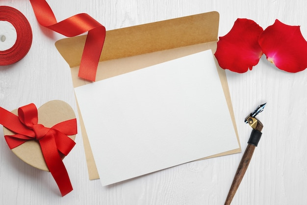 Mockup valentines day greeting card letter in envelope with kraft gift box red ribbon