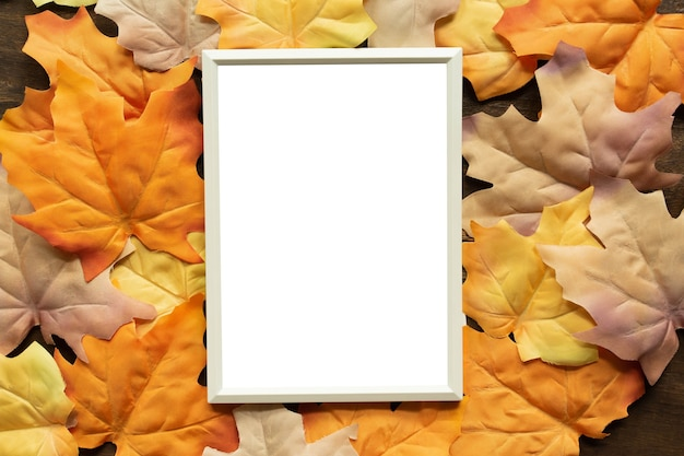 Mockup white blank paper frame with group of dried orange color maple leaves background